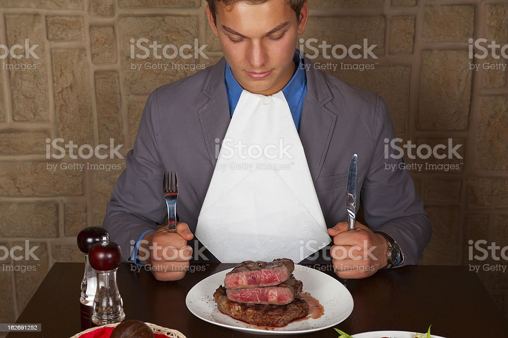 Man with utensils staring at his medium-rare steak royalty-free stock photo