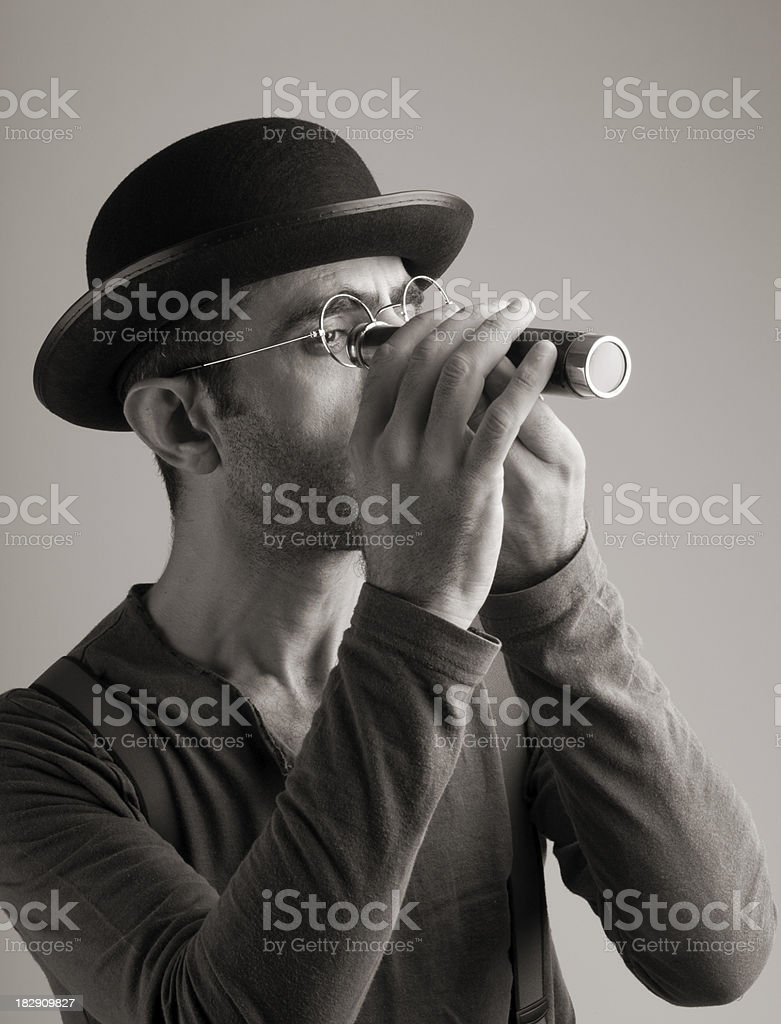 Man with vintage hat and suspenders looking through binoculars stock photo