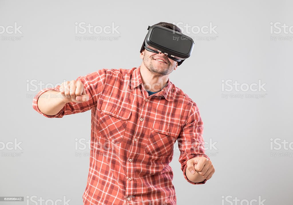 Man with virtual reality glasses paying bike simulator royalty-free stock photo