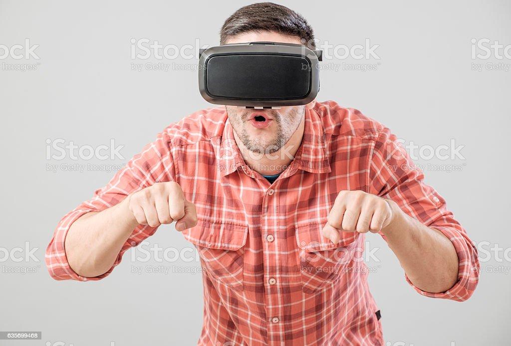 Man with virtual reality glasses paying bike simulator royalty-free stock photo