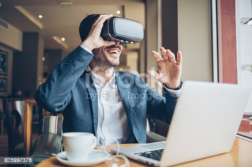 istock Man with virtual reality headset 625997378
