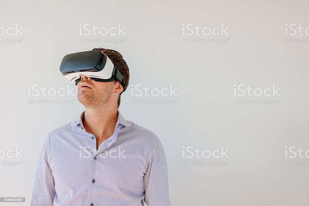 Man with VR headset looking away at the objects stock photo