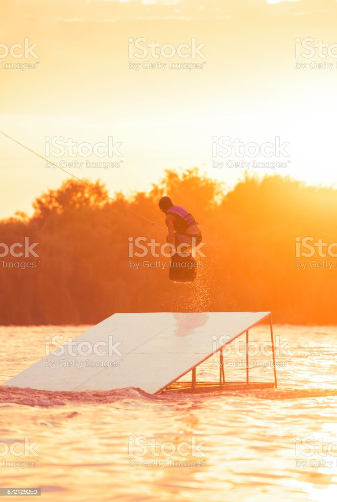 Man with wakeboard jumping in midair off ramp stock photo