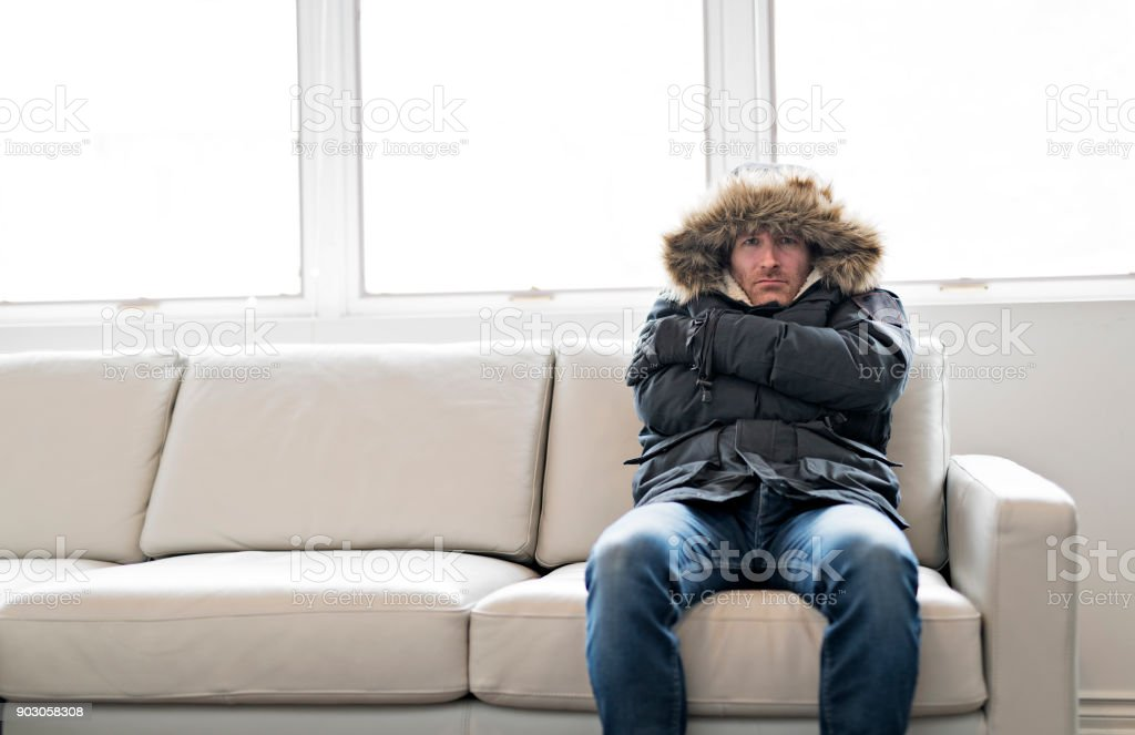 Man With Warm Clothing Feeling The Cold Inside House on the sofa stock photo