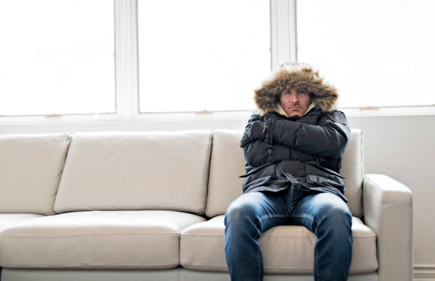 man with warm clothing feeling the cold inside house on the sofa - frozen stock pictures, royalty-free photos & images