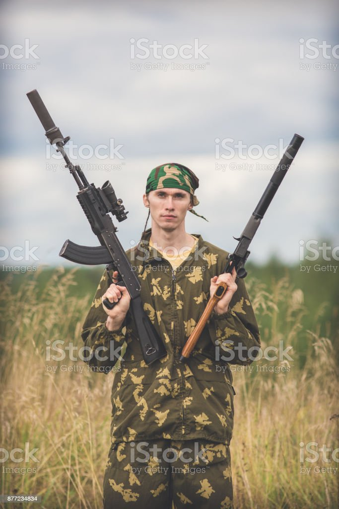 A man with weapons in both hands standing in a field stock photo