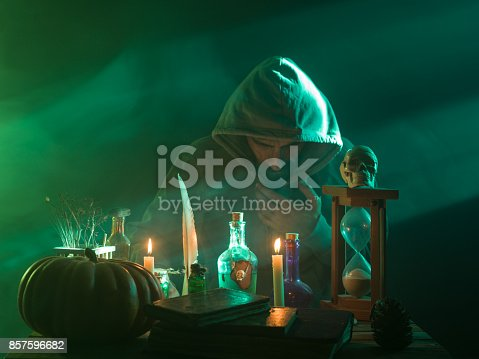 DSLR photo of man wearing a hooded coat making magic for halloween.There are pumpkin, poison bottle, dead insects, magic book, opium poppy, candles and human skull on desk in smoky and spooky atmosphere. The human skull is on top of hourglass. The light is colored in green and blue. A light beam is seen on the right side of frame.