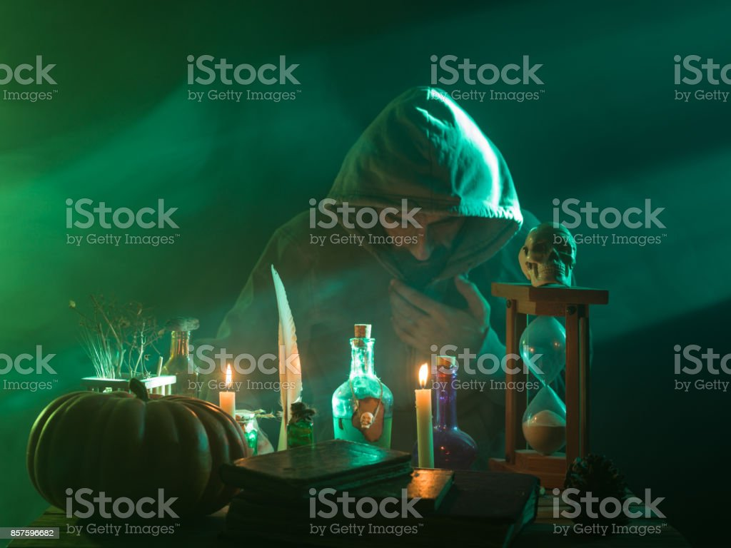 Man With Wearing A Hooded Coat Making Magic For Halloween stock photo