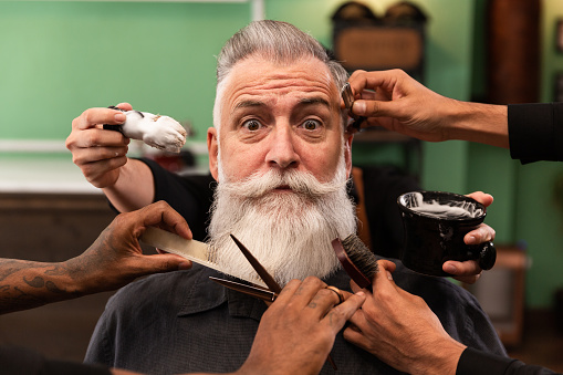 mature man with white beard looking at camera in barber shop with barber hands with cutting and shaving instruments, brush, scissors, comb, razor. hipster style