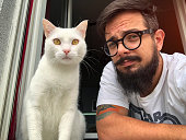 Man with tattoos With White Cat Making Selfie On The Window