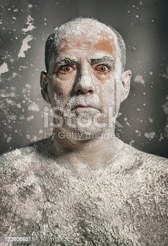 Man with white dust on body staring at camera