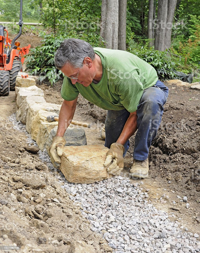Man with white hair building a stone wall in his yard royalty-free stock photo