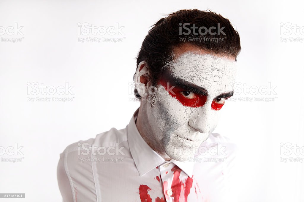 Man with white mascara and bloody shirt stock photo
