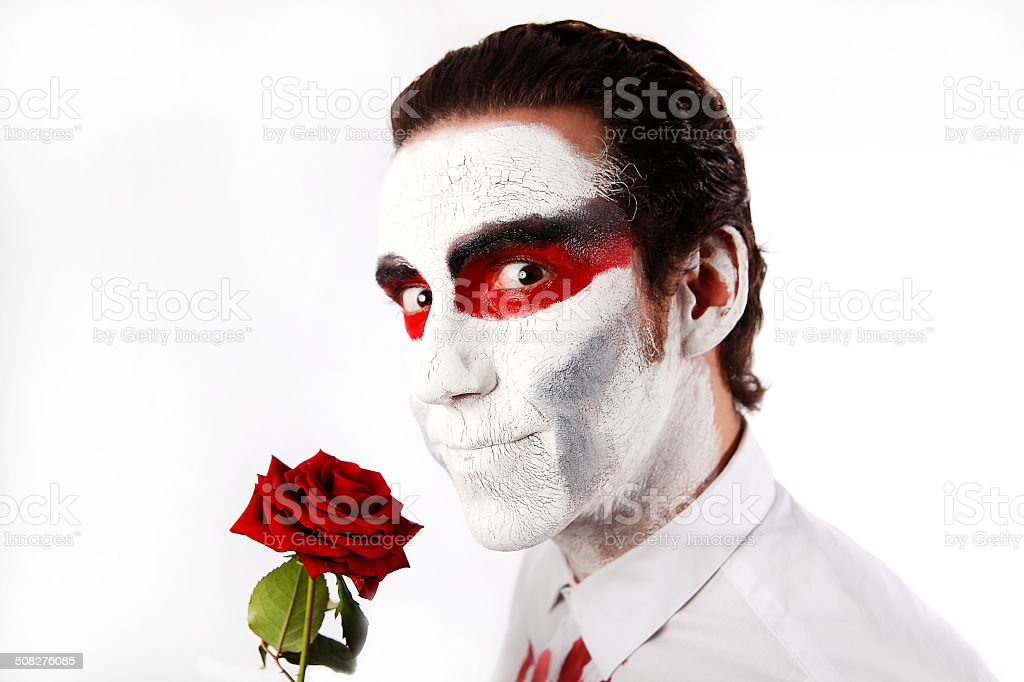 Man with white mascara and red rose stock photo