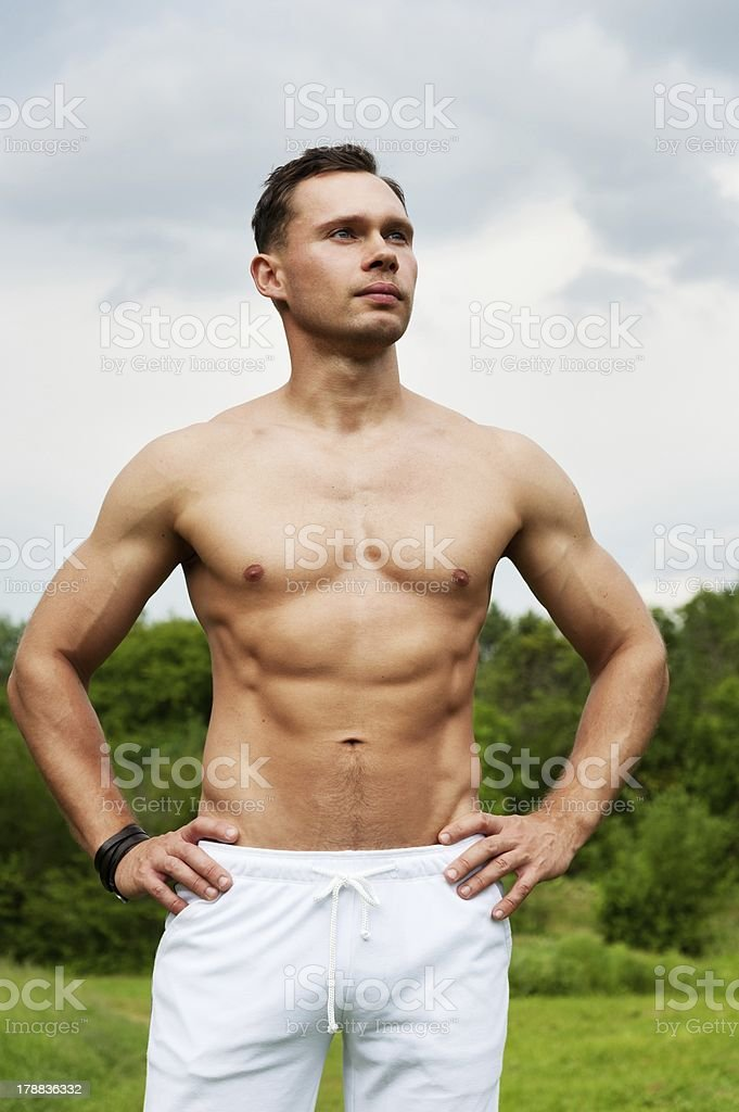 Man with white pants stands in park stock photo