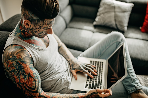 Man with whole body covered in tattoos using laptop at home
