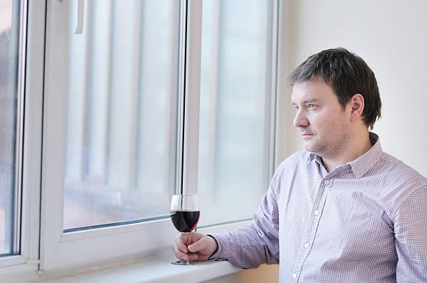 man with wine glass looking into the window - deplorable stock pictures, royalty-free photos & images