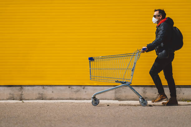 Man with with a shopping cart in front of a store, wearing a mask during a coronavirus pandemic / Covid-19. stock photo