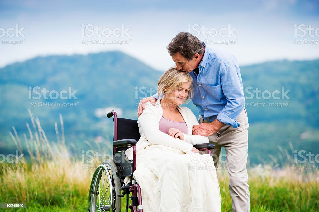 Man with woman in wheelchair stock photo