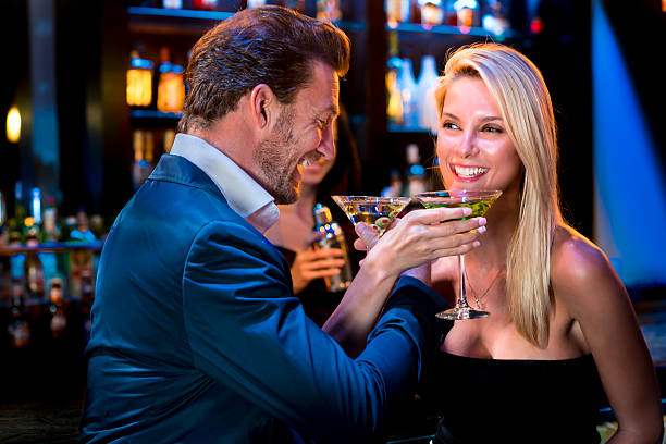 man with women drinking martinis at bar - young singles stock photos and pictures