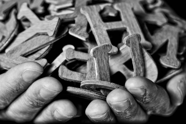 man with wooden letters in his hands closeup of the hands of a young caucasian man holding a handful of different wooden letters, in black and white illiteracy stock pictures, royalty-free photos & images