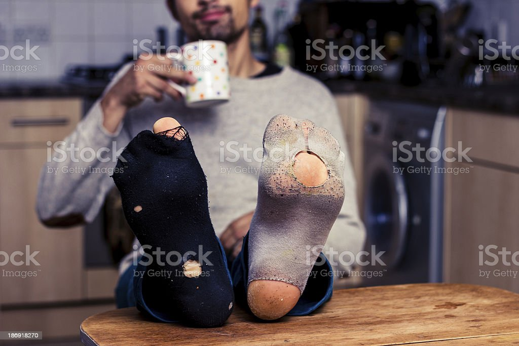 Man with worn out socks having coffee in kitchen stock photo