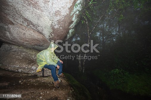 A man with yellow raincoat hiding from the rain under the rock shelter