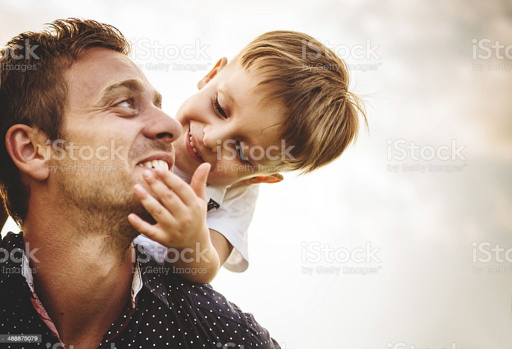 Man with young boy on shoulders stock photo
