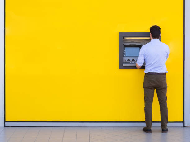 Man withdrawing money from an atm bank machine Man using a credit card in an atm for cash withdrawal banks and atms stock pictures, royalty-free photos & images