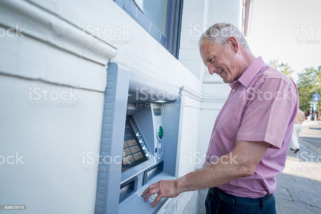 Man withdrawing money from an ATM stock photo