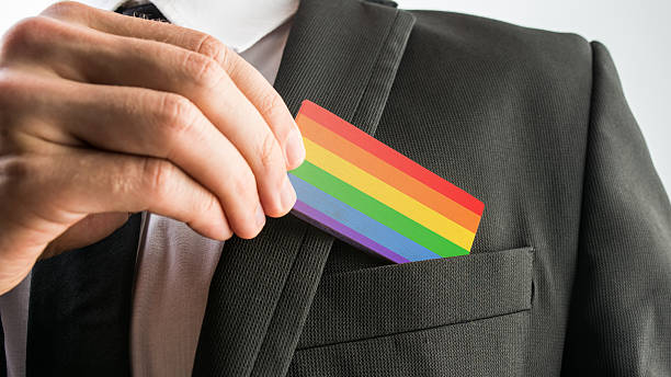 Man withdrawing wooden card painted as the gay pride flag Man withdrawing a wooden card painted as the gay pride flag from his suit pocket, close up of his hand. lgbtqi rights stock pictures, royalty-free photos & images