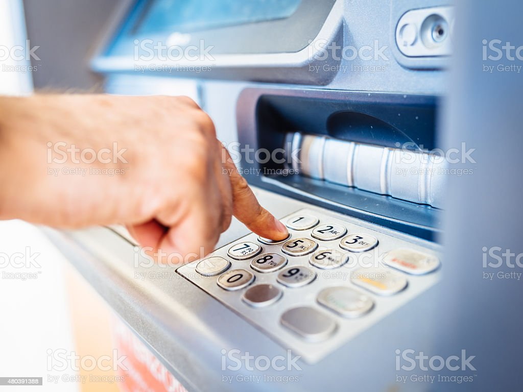Man Withdraws Money From An Atm stock photo