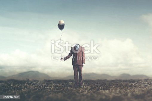 istock man without head holds black balloon with hat surreal concept 978257892