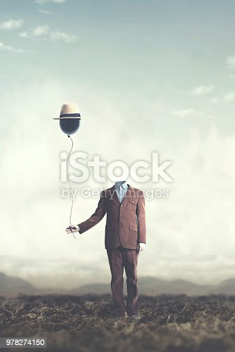 istock man without head holds black balloon with hat surreal concept 978274150