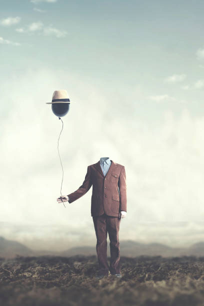 man without head holds black balloon with hat surreal concept man without head holds black balloon with hat surreal concept surreal stock pictures, royalty-free photos & images