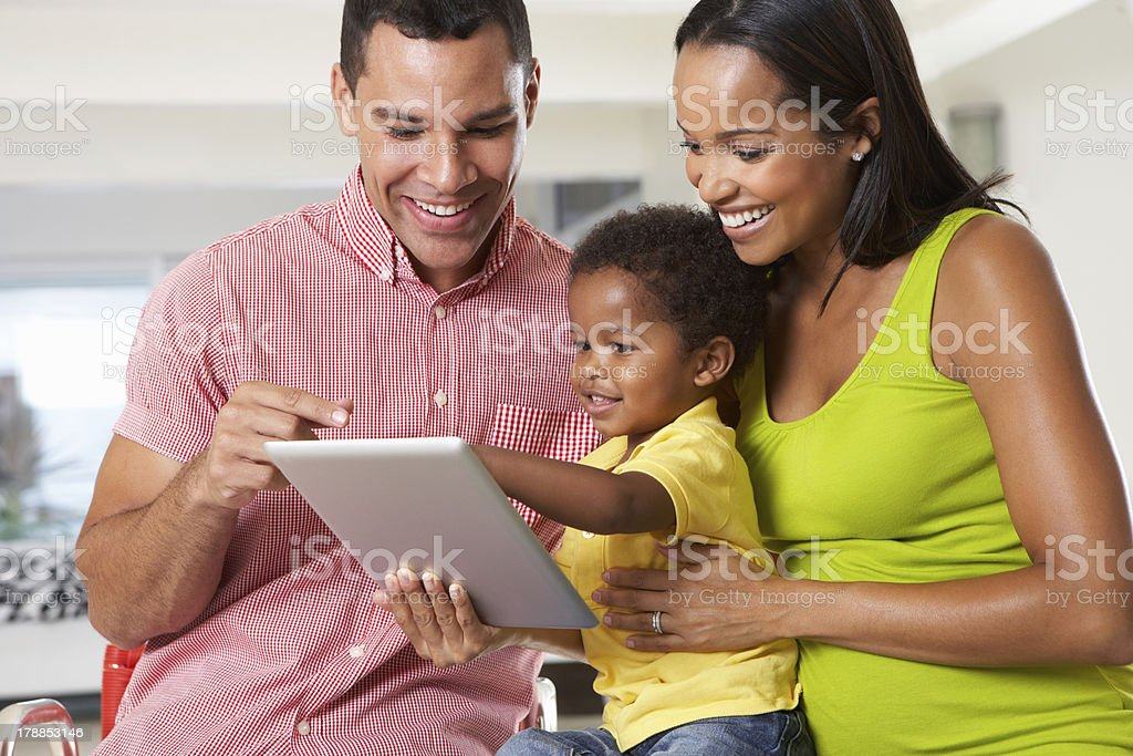 Man, woman, and child using a tablet in a white room royalty-free stock photo