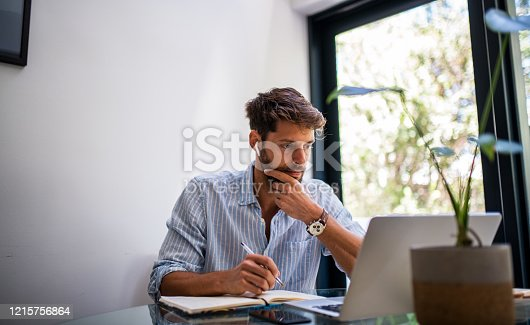 Young elegant man working from home.