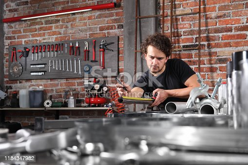 istock man work in home workshop garage measure metal with tape meter, marker iron pipe on the workbench full of wrenches, diy and craft concept 1184347982