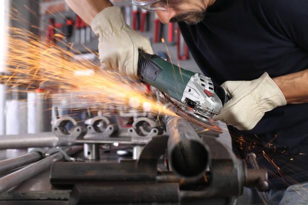 mann arbeiten in hauswerkstatt garage mit winkelschleifer, schutzbrille und bauhandschuhe, schleifen metall macht funken nahaufnahme, diy und handwerk konzept - schmirgelmaschine stock-fotos und bilder