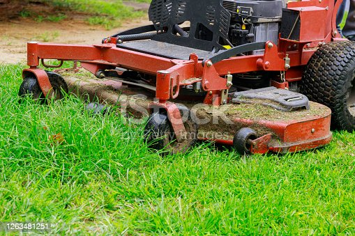 istock Man worker cutting grass in summer with a lawn mower 1263481251