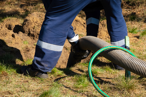 Man worker holding pipe, providing sewer cleaning service outdoor. Sewage pumping machine is unclogging blocked manhole