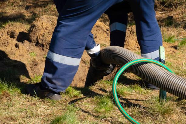 하수도 청소 서비스를 야외에서 제공하는 파이프를 들고 남자 노동자. 하수 펌핑 기계는 막힘 막힘 막힌 맨홀입니다. - 독성 물질 뉴스 사진 이미지