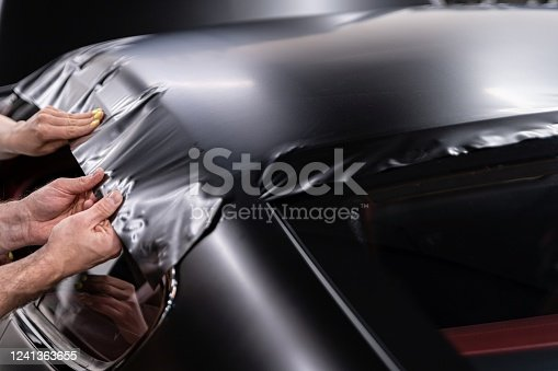 Man worker in car detailing studio applying color changing vinyl foil on car. Car wrapping