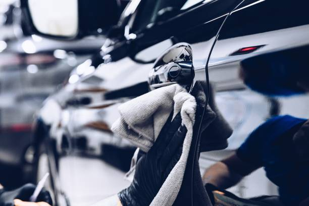 Man worker in car wash polishing car with cloth stock photo