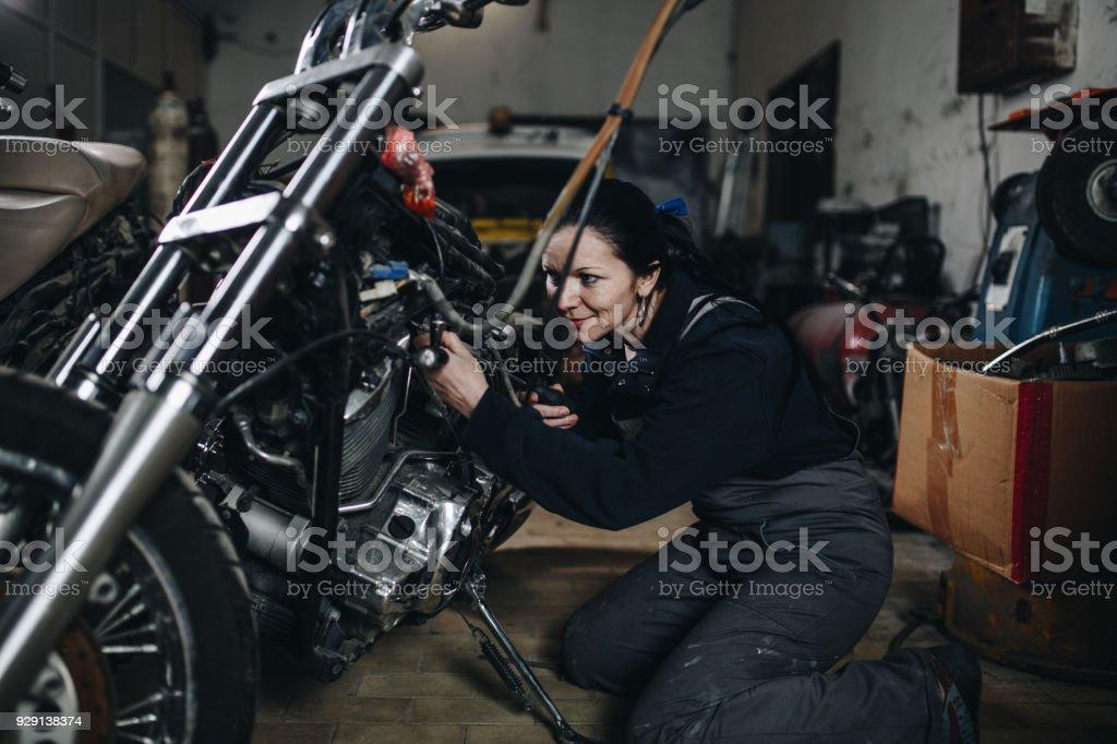 Man worker in motorcycle repair shop stock photo