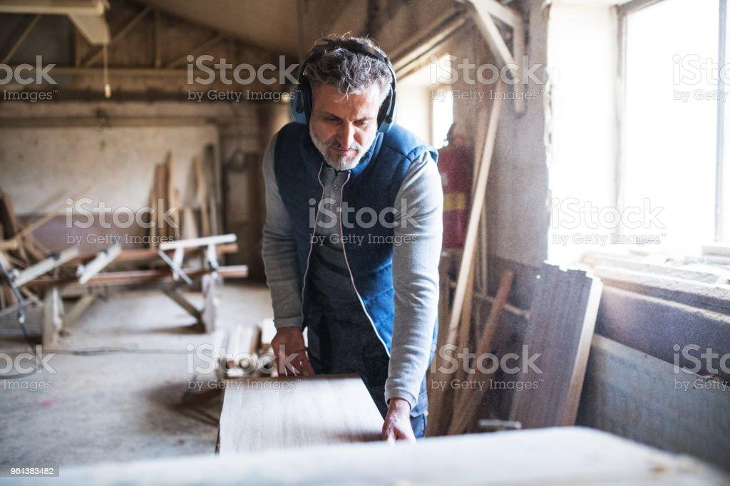 Een man werknemer in de Houtklas schooljaar, werken met hout. - Royalty-free Achtergrond - Thema Stockfoto