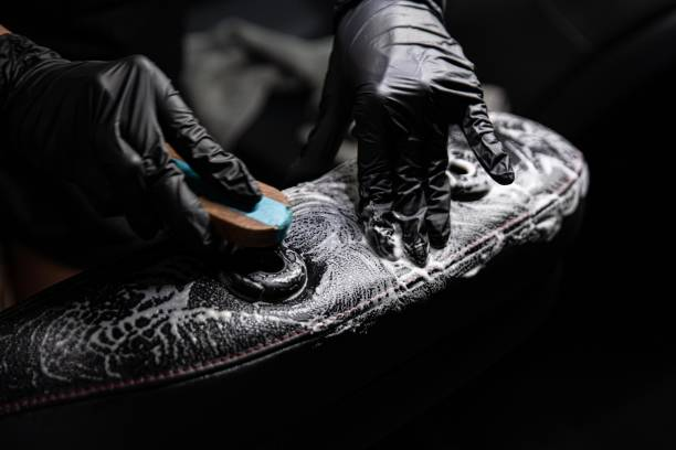 Mann Arbeiter der Autowäsche Reinigung Leder Autositz mit Bürste und Waschmittel – Foto