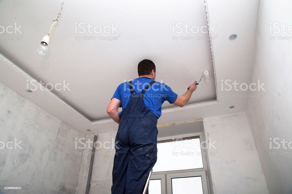 Man worker paints the ceilin inside of the room interior stock photo