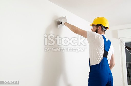 Man worker plastering wall with, man on ladder plastering the wall