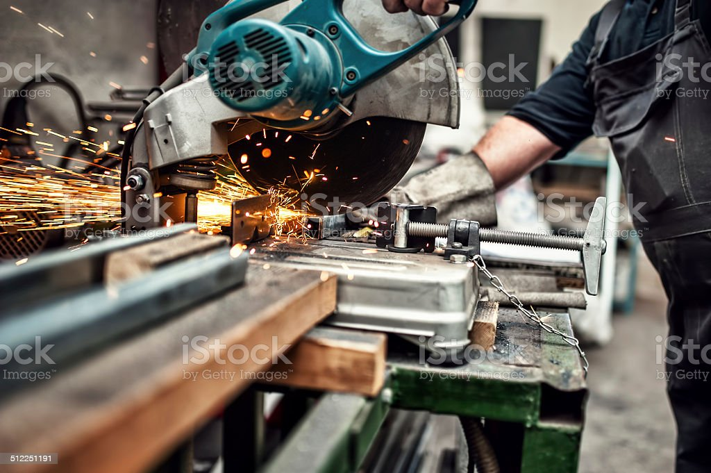 man, worker using a slinding compound mitre saw with blade stock photo